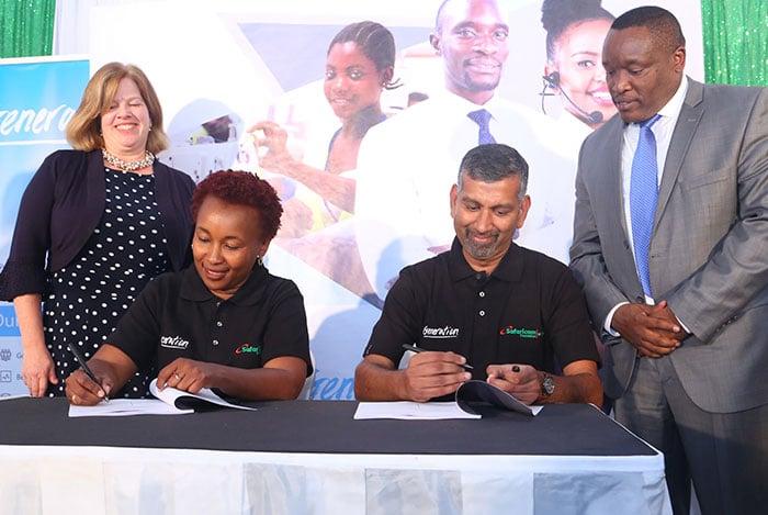 Safaricom Foundation's Sylvia Mwangi and Generation Kenya's Ramakrishnan Hariharan sign the partnership agreement as USAID's Heather Schildge and the Principal Secretary in the State Department of Post Training and Skills Development, Mr. Alfred Cheruiyot, look on